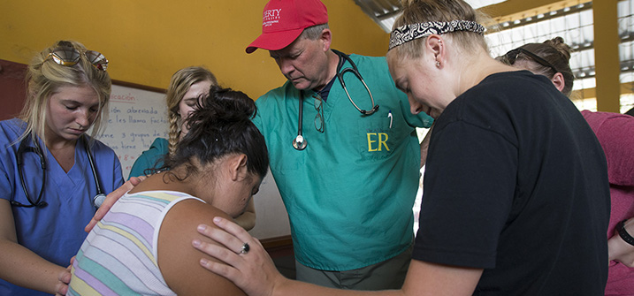 Sigmund P. Seiler, M.D., prays over a patient with student-doctors during medical outreach, Guatemala.