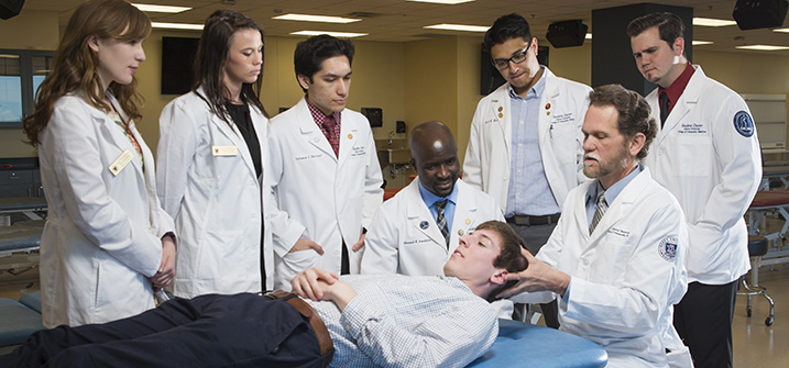 Peter A. Bell, DO, demonstrates Osteopathic Manipulative Treatment to LUCOM student-doctors.