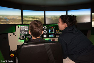 Guests are shown a flight simulator during a Liberty University School of Aeronautics event.