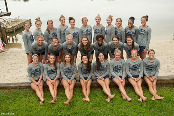 Members of Liberty University's NCAA Division I women's swim team pose from the beach of the Falwell's farm lake.