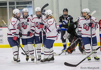 Lady Flames women celebrate a goal at the LaHaye Ice Center.