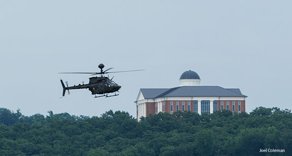 An army helicopter passes Liberty University's Center for Medical and Health Sciences as it prepares to land at Freedom Aviation.