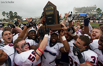 Liberty football players hoist the 2013 Big South Conference trophy.