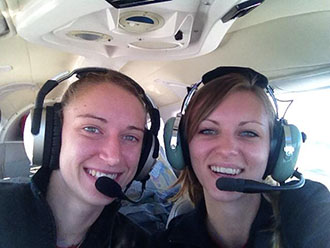 Megan Grupp and Jessica Dyer, coach of the Liberty Belles, pose in their cockpit.