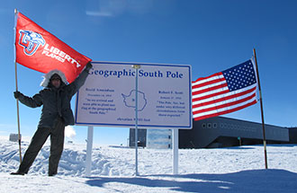 A Liberty University flag is flown at the Geographic South Pole.