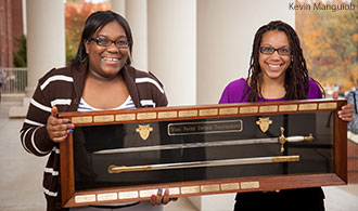 Liberty Debate Team members Vida Chiri and Meagan Edwards with the championship sword from West Point.