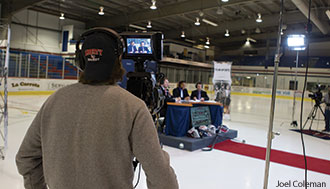 A Liberty student operates a camera during a hockey broadcast.