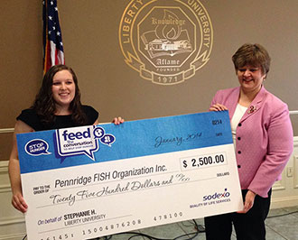 Cheryl Wolff presents check for Feed the Conversation at Reber-Thomas.