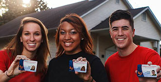 Liberty University students hold Flames Pass student ID cards.