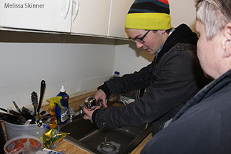 A Liberty University student installs a water filter in the home of a Flint, Mich., resident.