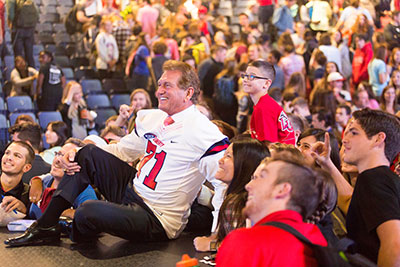 Joe Theismann, sporting a Liberty University jersey presented to him during Convocation, poses for a photograph on stage, backed up by a few of his fans. (Photo by Kaitlyn Becker Johnson)