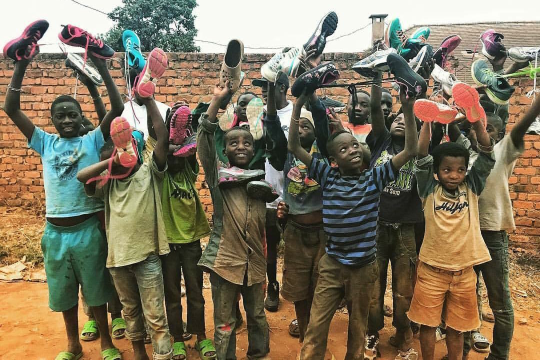 Congolese children celebrate as they are given shoes, collected at an event hosted by Liberty. (Photo by Christian Ntibonera)