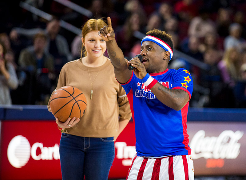 A Liberty student picked from the crowd receives tips from Globetrotter Jonte 'Too Tall' Hall before the 30-second challenge. (Photo by Jessie Rogers)