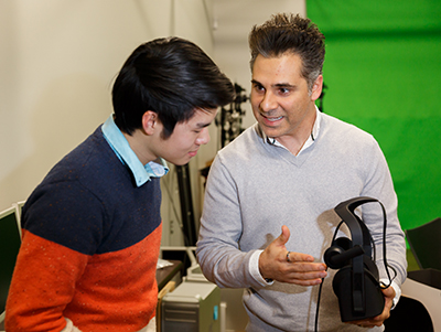 Kam Diba (right), president of Reverge, shows a high-tech VR headset to sophomore Wonbin Kang. (Photo by Joel Coleman)