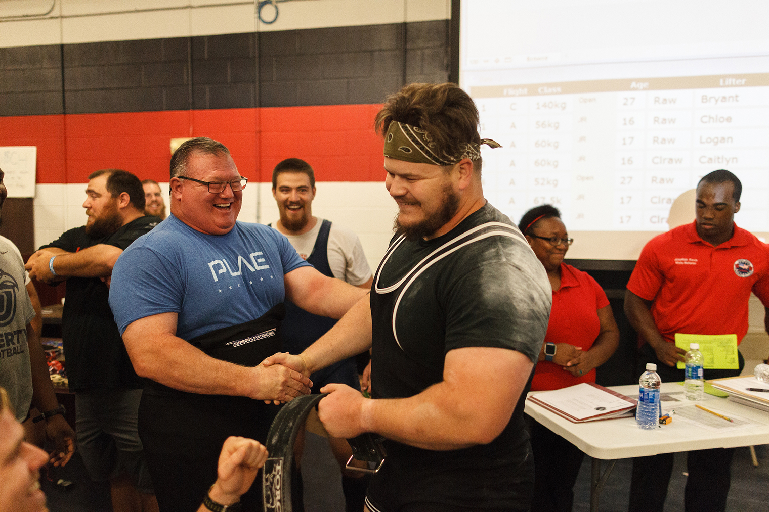 Liberty University Football Strength and Conditioning Head Coach Bill Gillespie (left) congratulates Assistant Coach Bryant Lewellyn after a successful lift, Saturday at the Football Operations Center weight room. (Photo by Joel Coleman)