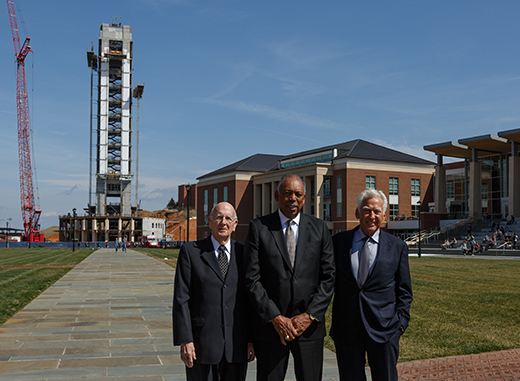 Bob Taylor (left), Wade Houston, and George Rawlings pose on Liberty's Academic Commons lawn with Freedom Tower and Rawlings School of Divinity under construction behind them.
