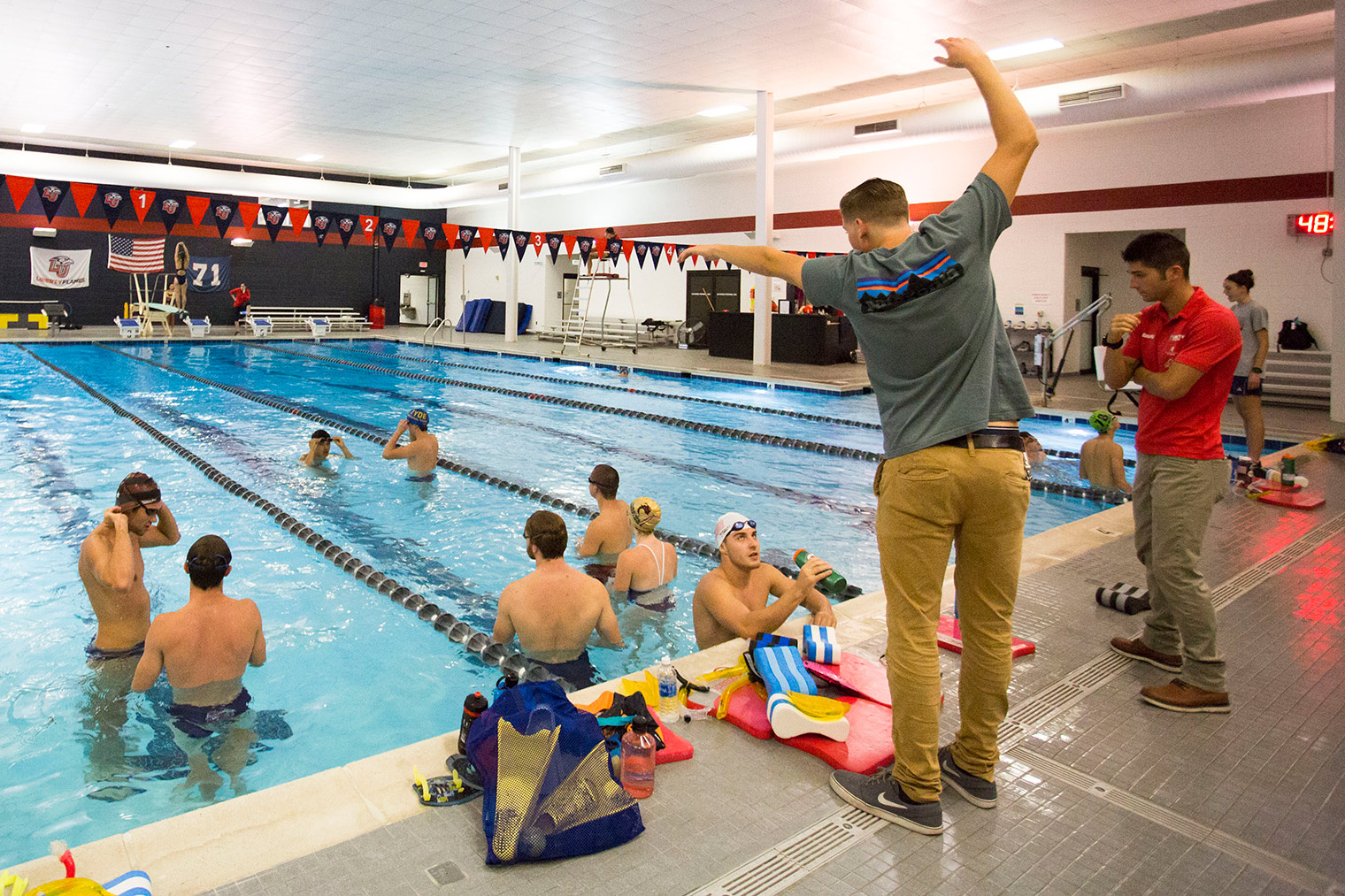 Liberty Assistant Coach Heath Grishaw Demonstrates Stroke Technique Beside  Head Coach Parker Spencer At The LaHaye Aquatics Center Pool.