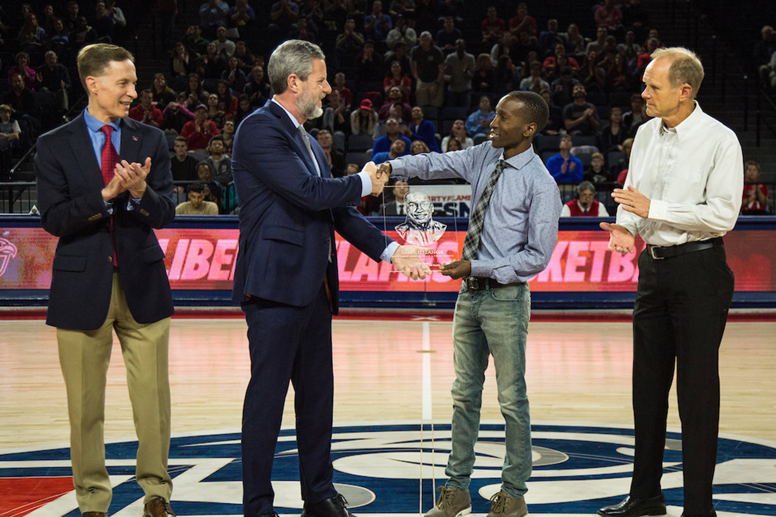 Sam Chelanga receives his plaque from Liberty University President Jerry Falwell beside Director of Athletics Ian McCaw (left) and Head Coach Brant Tolsma during Sunday's ceremony in the Vines Center, where the Athletics Hall of Fame is housed. (Photo by Leah Seavers)