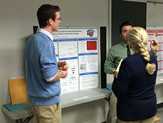Nathan MacGilvary and John Azra present their poster before a judge at the VAS Fall Meeting.