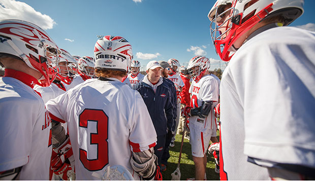 Flames head coach Kyle McQuillan (center) addresses his team in a huddle during the Feb. 17 season-opener played in frigid temperatures at the Liberty Lacrosse Complex. Liberty is moving up to Division I of the Men's Collegiate Lacrosse Association after reaching the MCLA Division II national semifinals this year. test test test test