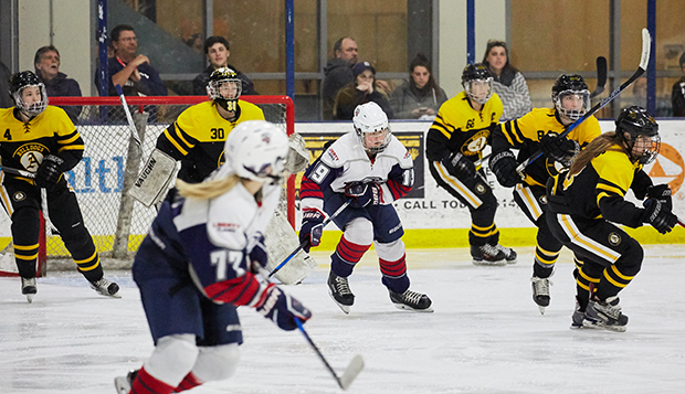 Lady Flames forward Shannon Fehr and defenseman Sydney Pierce are surrounded by Bulldogs in the 2018 ACHA DI national championship game in Columbus. (Photo by Joel Coleman) test test test test