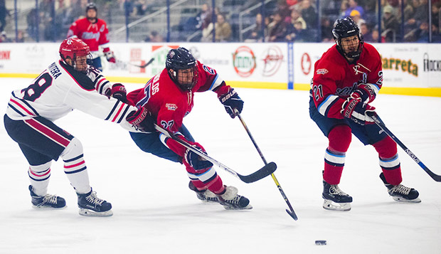 Liberty junior defenseman Basil Reynolds skates between Rutgers forward Griffin Privitera and Flames freshman forward Devin Pierce. (Photo by Kevin Manguiob) test test test test