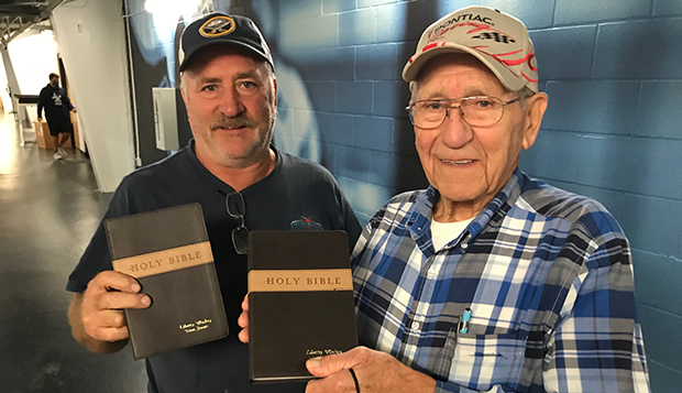 Brian Lowman and his father, Ray, display samples of the King James Version Bibles they presented to the team. test test test test