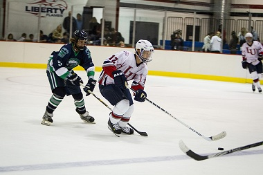 Christian Garland (#12) leads an attack for the Liberty Flames Division I hockey team as they face the Hampton Jr. A Whalers in their season opener at the LaHaye Ice Center Friday night. Garland put two in the net in the Flames' 9-1 victory. (Photo by Colin Mukri)