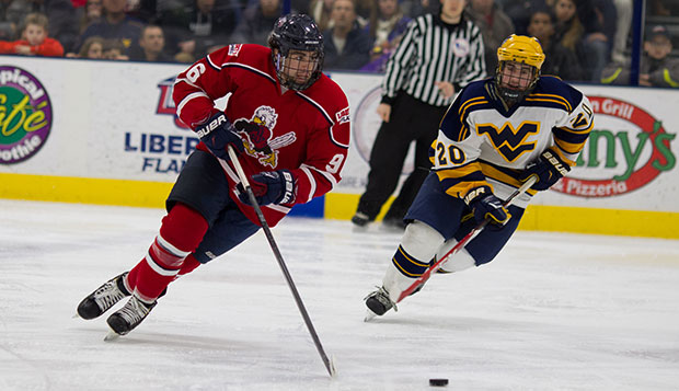 Liberty junior defenseman Steven Bellew skates the puck past West Virginia forward Gerard Clayton at the LaHaye Ice Center. test test test test