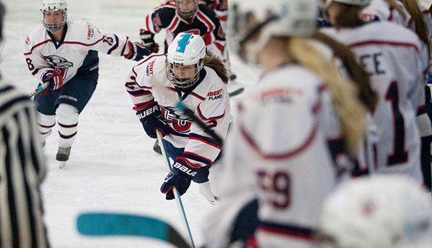 Liberty freshman forward Lauren McDonald (2) skates along the boards in front of the Lady Flames' bench, flanked by sophomore forward Chelsey Greenwood (18) at the LaHaye Ice Center. test test test test