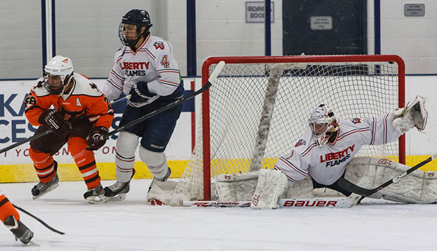 Liberty senior goalie Justin Gortman looks to make a save as defenseman Lucas Ebel (left) ties up with a Virginia Tech forward. test test test test