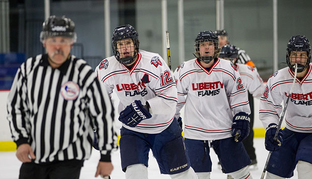 Liberty senior forward Brad Docksteader (left) and freshman forwards Jordan Barstead and Devon Docksteader celebrate the first goal, Sunday at the LaHaye Ice Center.  test test test test
