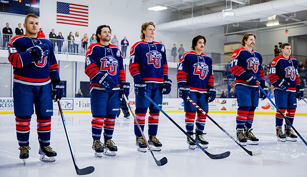 Flames seniors (from left) Josh Bergen, Josh Hamilton, Victor Blomberg, Zechariah Roberts, Chaydan Lauber, and Cody Clarke stand for the National Anthem before a recent game at the LaHaye Ice Center. (Photo by Ellie Richardson)  test test test test