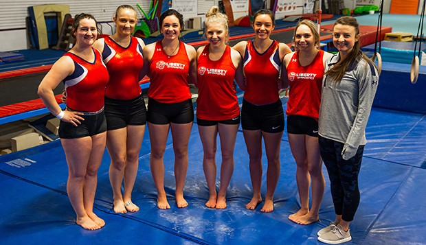 The Lady Flames' women's gymnastics team poses with Assistant Coach Jessica Hogue. (Photos by Jessie Rogers) test test test test