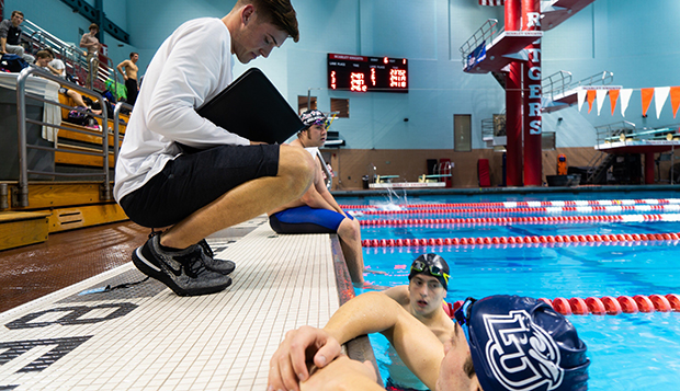 Flames Head Coach Heath Grishaw instructs freshman swimmer Dan Flittner from the pool deck at Rutgers. (Photo courtesy of Tariq Kelly) test test test test
