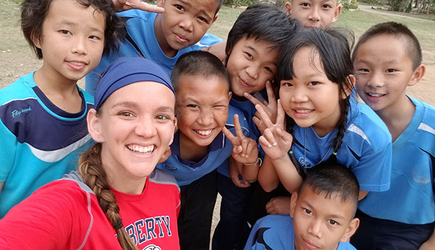 Hilary Kline, a senior majoring in social work, takes a selfie with a group of youth she taught Ultimate to in Thailand.