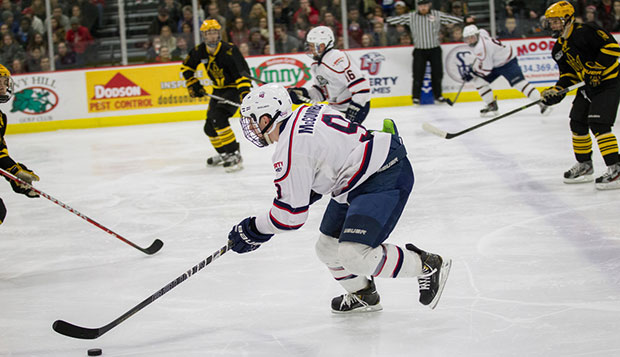Liberty senior forward and captain Andrew McCombe skates through the Sun Devils' defense at the LaHaye Ice Center. test test test test