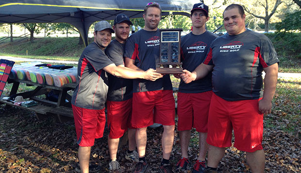 Flames head coach Steve Bowman (center) and his players pose with the Northeastern Collegiate Disc Golf Championships trophy after Sunday's final round of competition. test test test test