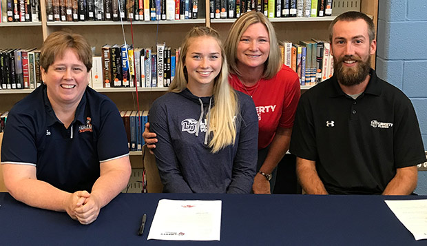 Marabeth Hammersmith (center, with her mom) signs her letter of intent to attend Liberty this fall at a ceremony at Heritage High School, attended by her coach Kelly Bryant as well as Flames Head Coach Kaleb VanDePerre. test test test test