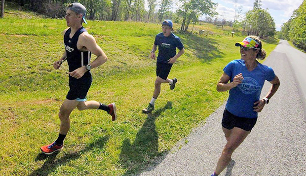 Flames sophomore Max Galbraith (left) and graduate student Mark Fairley run the final marathon leg on the grass while Liberty triathlon Head Coach Heather Gollnick encourages them from on the pavement Wednesday at Smith Mountain Lake State Park. test test test test