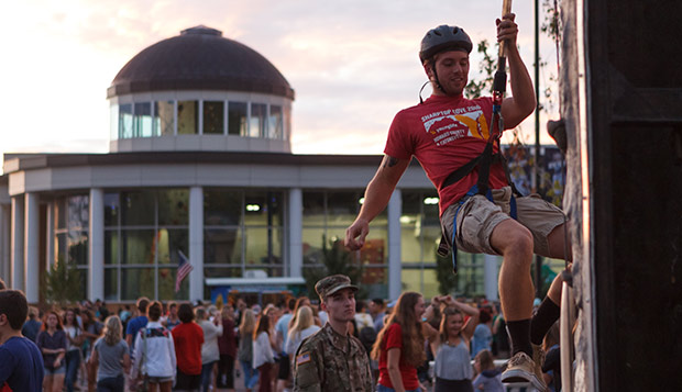 With the LaHaye Recreation and Fitness rock climbing tower in the background, a Liberty student attempts to rappel the tower set up in the LaHaye Ice Center parking lot at last year's Block Party. (Photo by Nathan Spencer) test test test test
