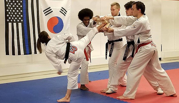 Senior Sadie Newton breaks a board held by teammates and assistants during testing for her 4th Dan black belt promotion. test test test test
