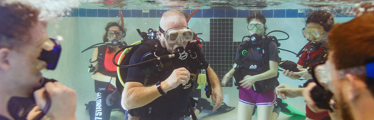 Instructor and students in pool wearing SCUBA gear