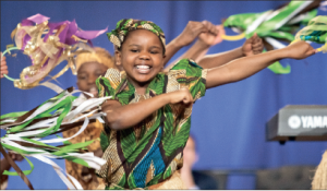 A joyful noise — The Children of the World choir performed in the Schilling Center, singing cheerfully and sharing messages of how their lives had changed through child sponsorship. Photo credit: Ruth Bibby
