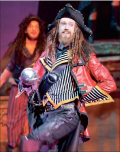 To Neverland — The play's villain, Captain Hook, played by Nelson, causes chaos for the band of travelers. Photo credit: Ruth Bibby