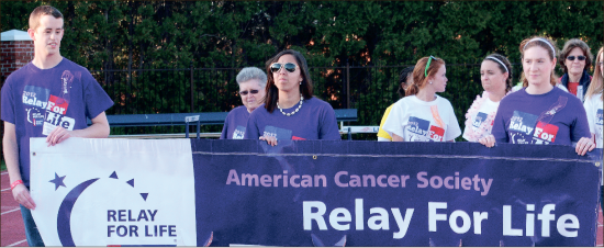 Victory lap— Liberty student Josh Isaacson (far left) partakes in the Relay for Life Survivor Lap, where cancer survivors and their caretakers celebrated their victory over the disease to the applause and cheers of other relay participants. Photo credit: Victoria Pearce