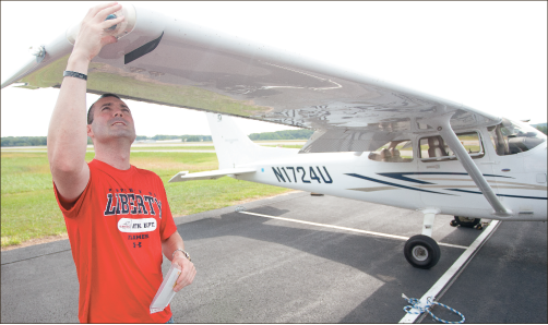 Pilot — Aviation student Steve Barkof examines his aircraft during the pre-flight check at Freedom Aviation. Photo credit: Ruth Bibby