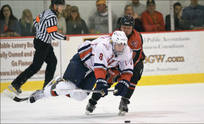 Effort— Senior defenseman Scott Morongell leaps to clear the puck against a Davenport player. Photo credit: Ruth Bibby