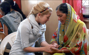 India — Kalley Long prays with a woman during the two-week long trip. Photo provided