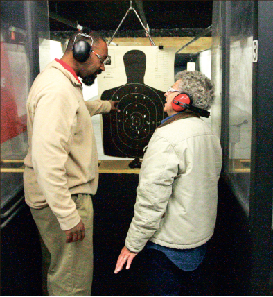 Control — Chuck Thomas instructs a friend at Lynchburg Arms and Indoor Shooting Range. Photo credit: Ruth Bibby